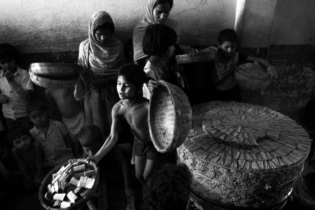 Child labors submit prepared bidi (leaf-rolled cigar made by tobacco prepared for smoking) to a factory contractor inside a factory at Sulitala village, Murshidabad 350 km north from the eastern Indian city of Kolkata, February 08, 2010.